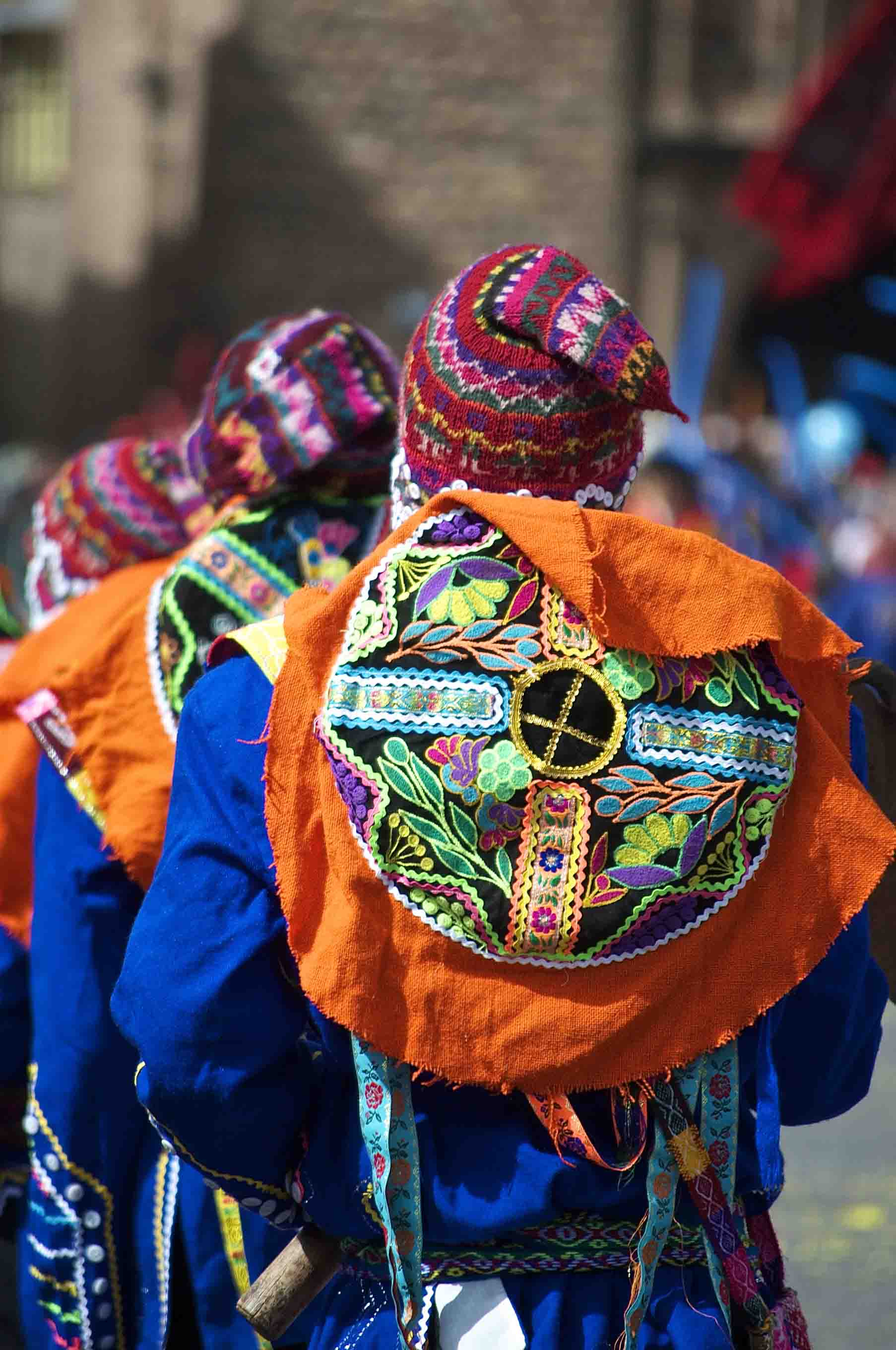 The backs of costumed young men dancing in the traditional Inti Raymi festival in Cusco, Peru.  Inti Raymi is the annual festival celebrating Incan culture in Peru, and involves traditional dress and dances in the central Plaza de Armas of Cusco.