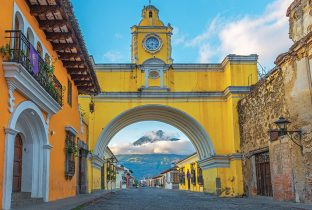 The colorful yellow arch of Antigua city at sunrise with the active Agua volcano in the background, Guatemala shutterstock_769879639 770x508pxl