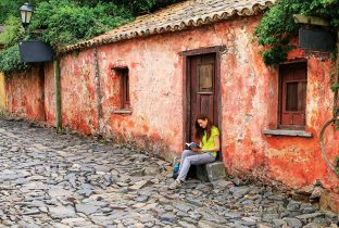 Young woman sitting at Calle de los Suspiros (Street of Sighs) in Colonia del Sacramento, Uruguay. It is one of the oldest towns in Uruguay - Image shutterstock_1046927164 770x508pxl